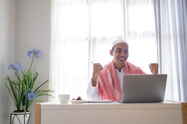 De opgewekte succeszakenman heft zijn wapen op tijdens het gebruik van laptop