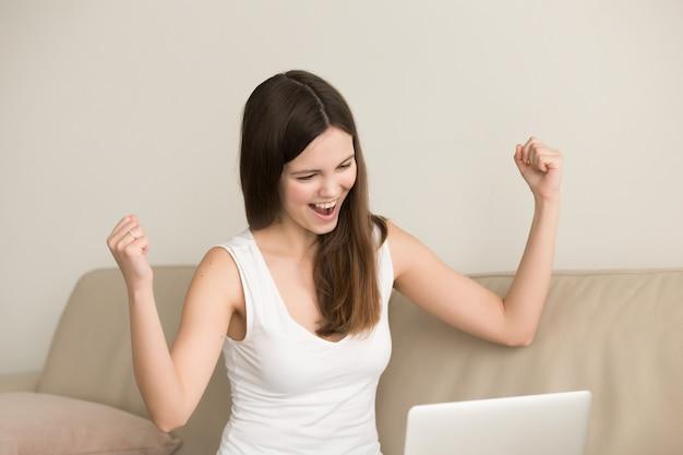 De opgewekte vrouw zegt ja terwijl het kijken op laptop