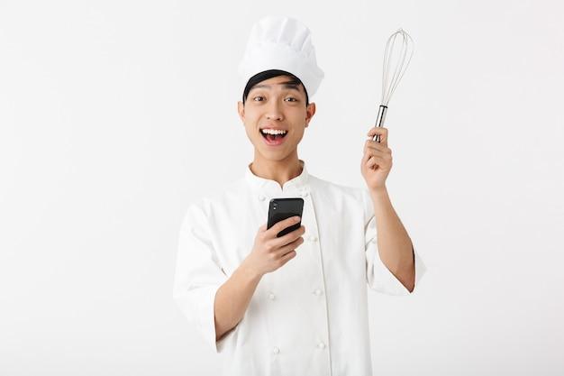 De opgewonden aziatische chef-kok die eenvormige status draagt die over witte muur wordt geïsoleerd, die mobiele telefoon met behulp van, zwaait toont