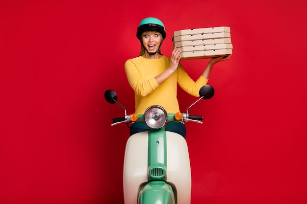 De opgewonden geschokte fiets van de de koerierrit van de studente leveren de doos van de voedselpizza op rode muur