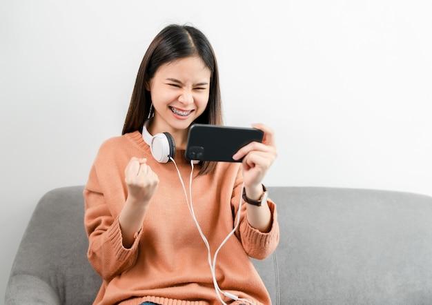 De opgewonden jonge aziatische vrouw draagt witte hoofdtelefoon