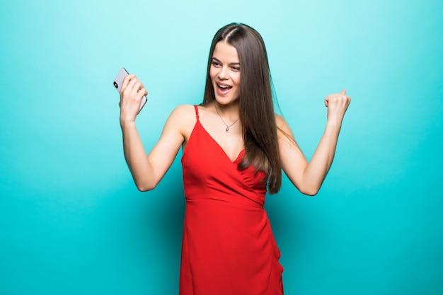 De opgewonden jonge vrouw in rode kleding maakt winnaargebaar status geïsoleerd over blauwe muur