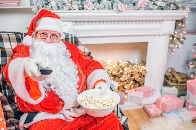 De opgewonden kerstman zit bij de open haard en heeft een afstandsbediening en een bak popcorn.