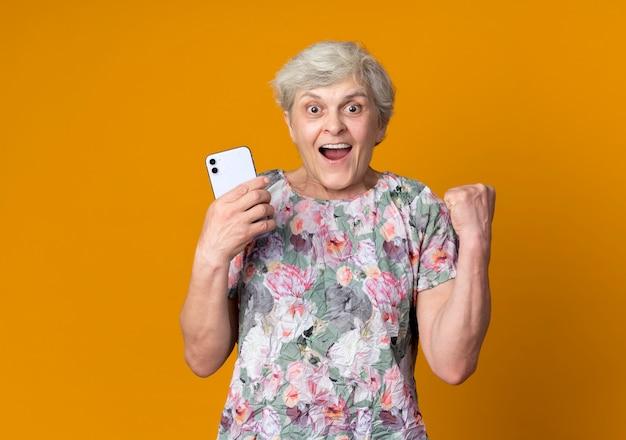 De opgewonden oudere vrouw heft de telefoon van de vuistholding op die op oranje muur wordt geïsoleerd