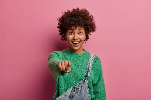 De opgewonden positieve vrouw heeft een afro-kapsel, wijst de wijsvinger rechtstreeks naar je, ziet iets heel grappigs, draagt een groene trui en een overall, geïsoleerd op een roze pastelkleurige muur. wauw geweldig