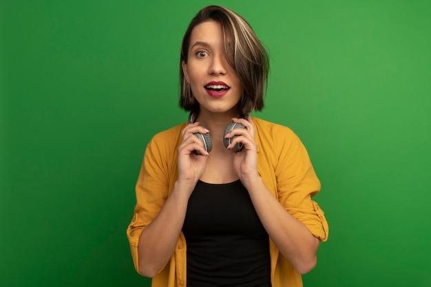 De opgewonden vrij kaukasische vrouw houdt geïsoleerde hoofdtelefoons