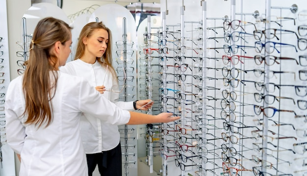 De opticien helpt vrouwelijke cliënt om glazen in optiekwinkel te kiezen