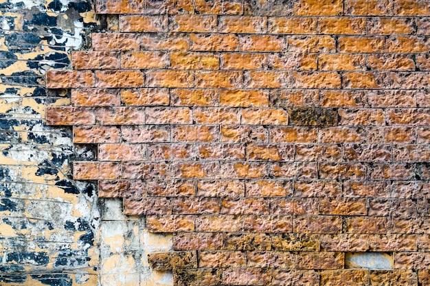 De oranje bakstenen muur is barst en breek en wordt gecorrodeerd door regenwater