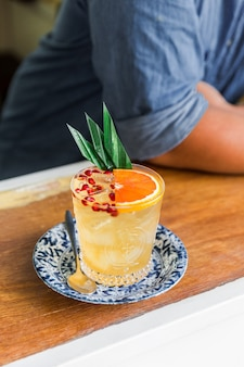 De oranje fruitige cocktail die zich vermengt met gesneden sinaasappel- en granaatappelpulp in een drinkglas.