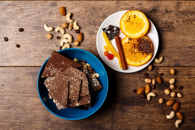 De oranje kaneel en de noten van het chocoladesuikergoed op hout