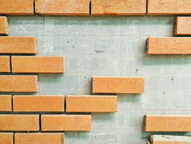De oranje stenen staan opgesteld aan de muur, kopie ruimte.