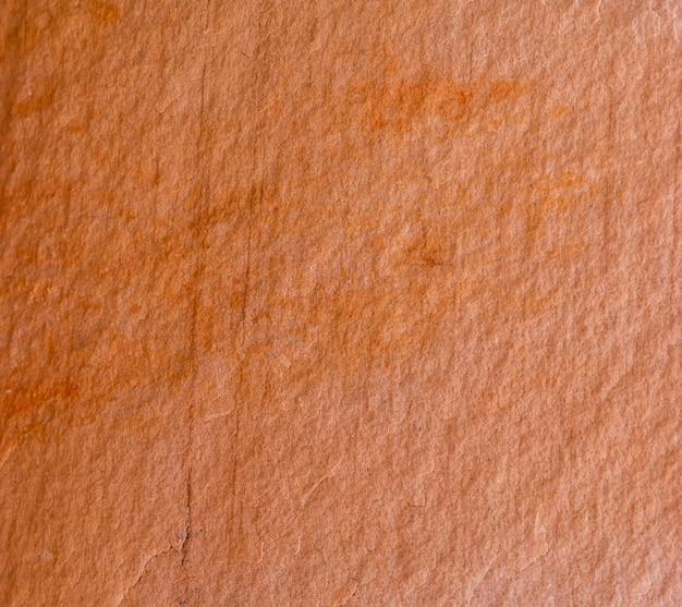De oranjerode oppervlakte van de rotslaag voor textuurachtergrond