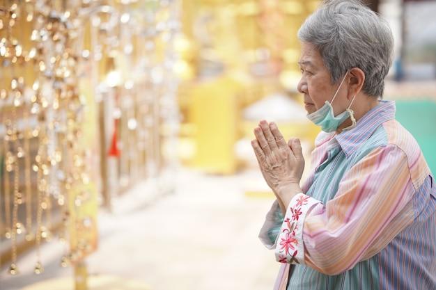 De oude aziatische oudere toerist die van de vrouwenreiziger bij boeddhistische tempel bidden.