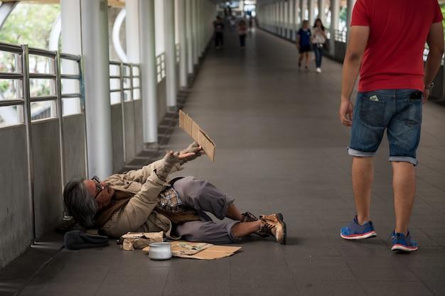 De oude dakloze man smeekt om geld