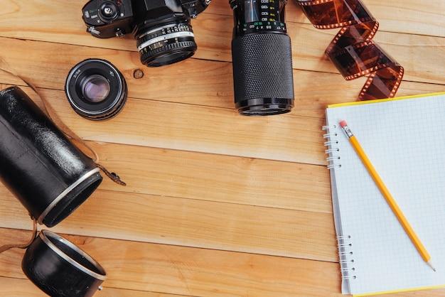 De oude filmcamera en roll film en notebook met potlood op een houten