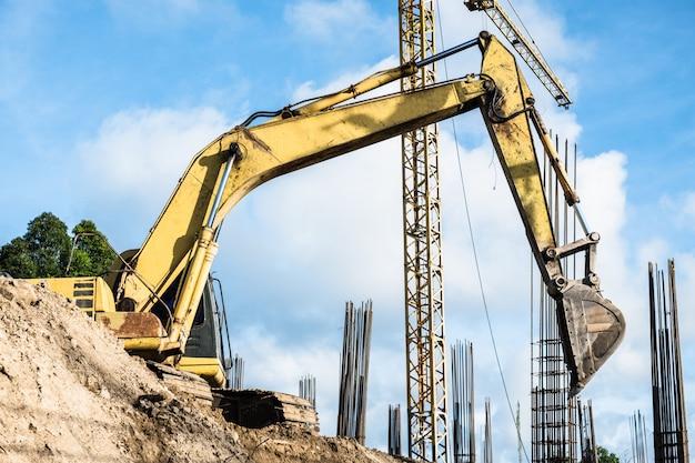 De oude gele backhoe of graafwerktuig graaft grond bij nieuwe bouwconstructieplaats met staal concrete pijlers in de rug.