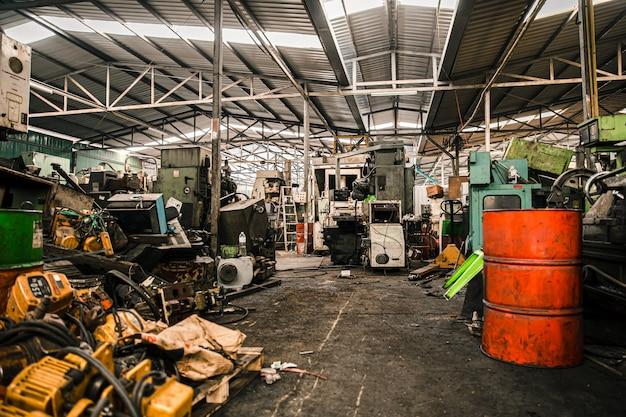 De oude grunge gebruikte garage van de machineswerkplaats of het zware werkplaats van het het pakhuisgevaar van de machineafvalhof.