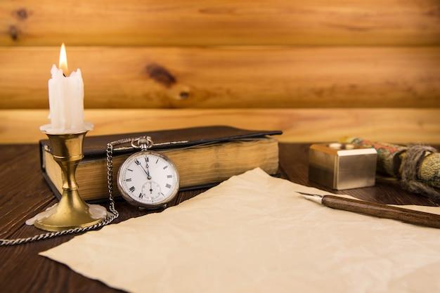 De oude handvatveer en een vel papier met een kaars