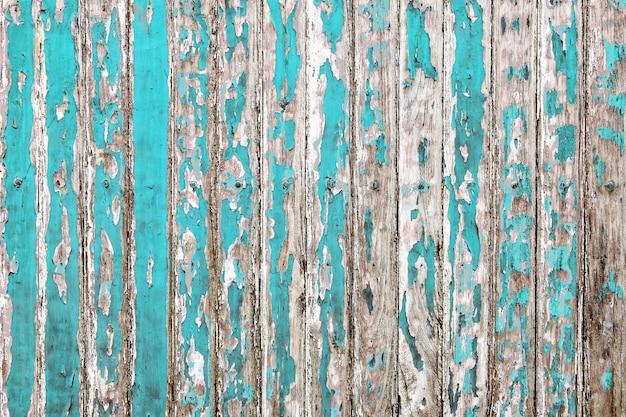 De oude houten muur schilderde met bleke cyaankleurenschil geopenbaarde rustieke textuurachtergrond