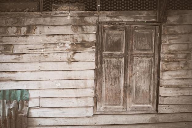 De oude houten ramen aan de houten wanden en de verzinkte platen gaan achteruit.