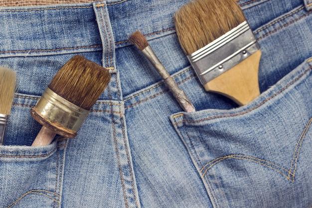 De oude hulpmiddelen van de huisreparatie in jeanszakken.