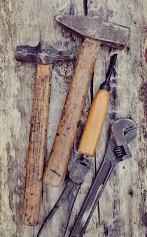 De oude hulpmiddelen van de timmerman op een houten lijst