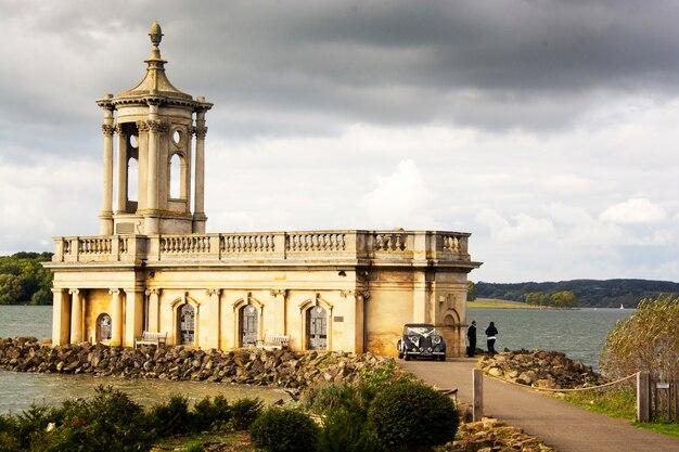 De oude kerk engelse bouw met toren bij het meer.