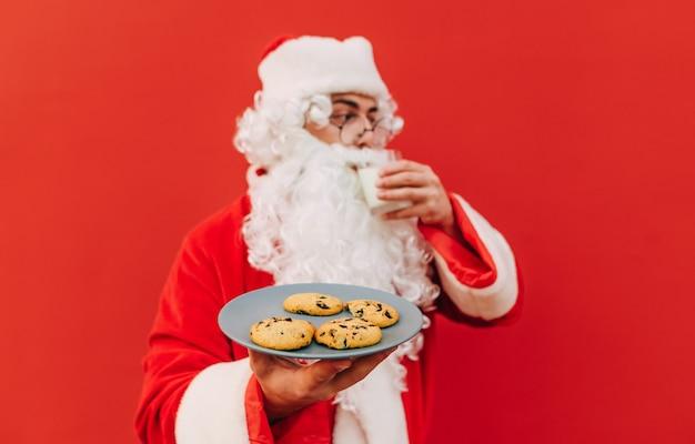 De oude kerstman houdt een bord met lekkere koekjes vast