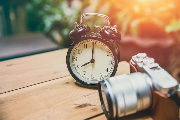 De oude klok met retro camera houdt tijd en geheugenconcept