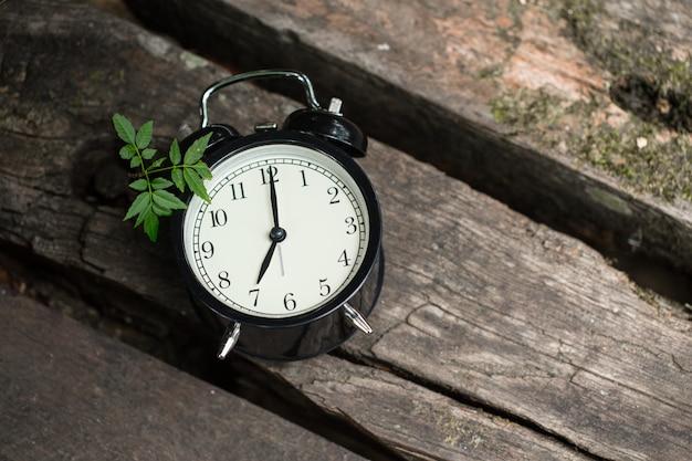 De oude klok retro stijl toont 7 uur op hout op de bosachtergrond.