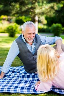 De oude man die van smiley zijn vrouw bekijkt