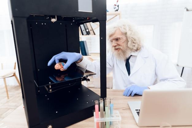 De oude man experimenteert met een 3d-printer.