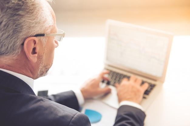 De oude man gebruikt laptop terwijl hij in zijn kantoor werkt.