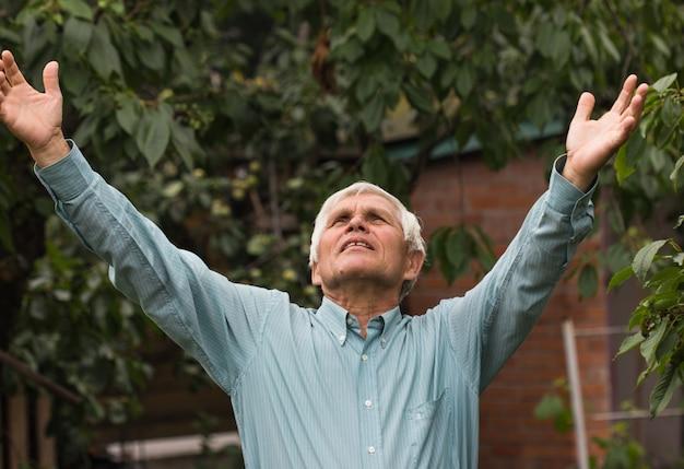 De oude man hief zijn handen op naar de ondergaande zon. geweldig uitzicht over de vallei