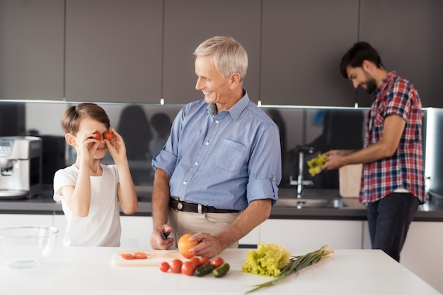 De oude man in een blauw shirt bereidt een salade voor.