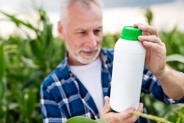 De oude man in een veld kijkt op een fles in zijn handen. kunstmestflesmodel
