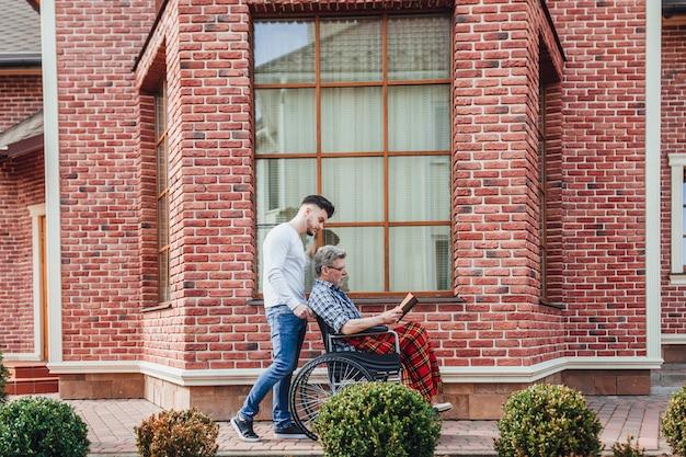 De oude man op een rolstoel en zijn volwassen zoon lopen in het verpleeghuis gaden