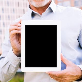 De oude mens die van de close-up een tabletmodel houdt