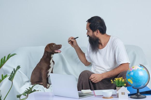 De oude mens speelt met een huisdier terwijl thuis het werken aan bank.