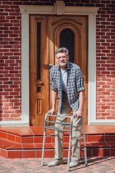 De oude mens zit op rolstoel kijkend uit aan van de camera
