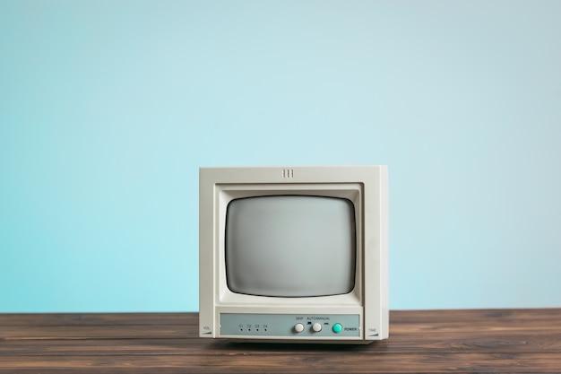 De oude monitor op een houten tafel op een blauwe achtergrond. vintage elektronica.