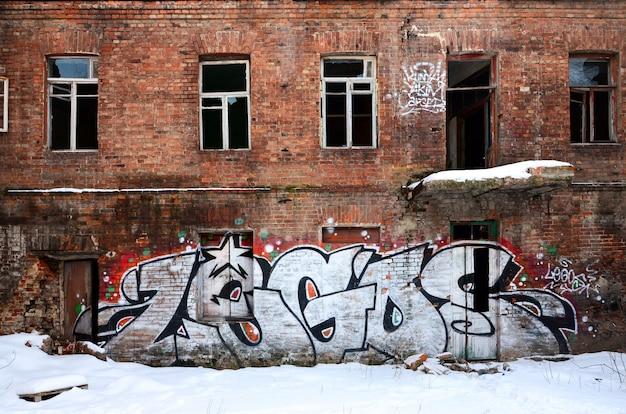 De oude muur, geschilderd in kleurengraffiti die rode aerosolverven trekt.