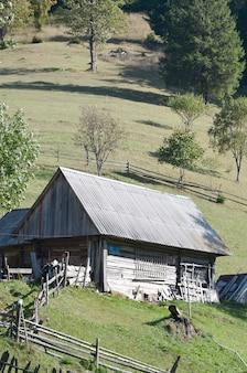De oude oekraïense hut met een dak in leisteen en een houten hek in een groen veld