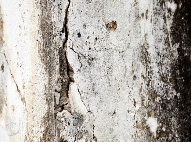 De oude oude cementmuur met gekleurde schil openbaarde bevlekte rustieke textuurachtergrond