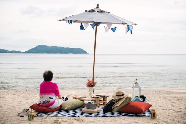 De oude pensionvrouw zit op strandpicknick in phuket, thailand