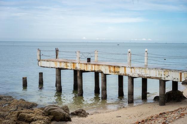De oude pier ligt naast de rustige, blauwe zee. het is een gevaarlijke plaats om binnen te komen.