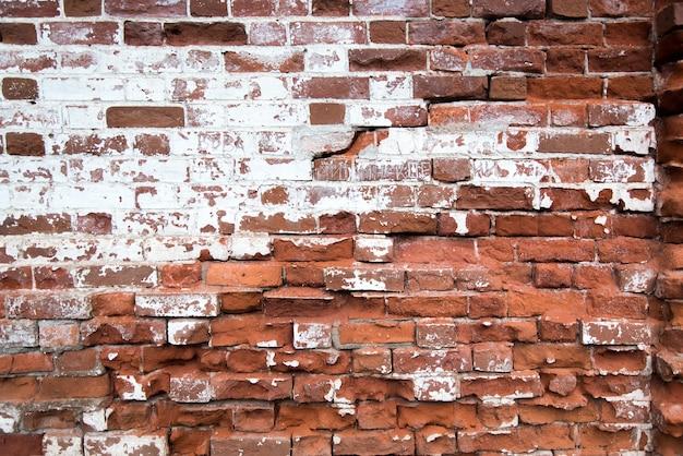 De oude rode achtergrond van de bakstenen muurtextuur. gevel van het huis.