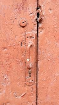 De oude rode textuur van het deurhandvat.