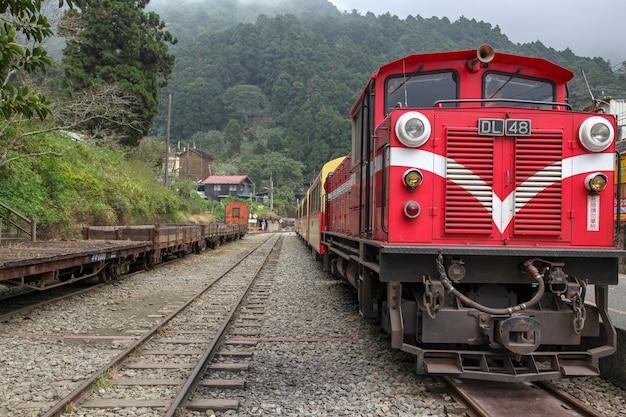 De oude rode trein in alishan-lijn (bergafwaarts) komt op mistige dag terug naar chiyi-station.