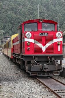De oude rode trein in alishan line komt op mistige dag terug naar het treinstation van chiyi.